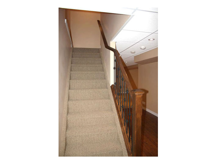 Oak railing and berber carpet for basement stairs
