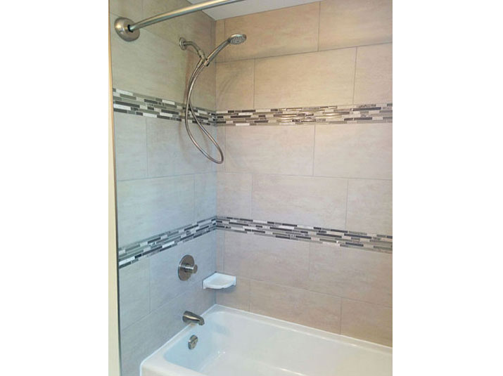 Bathtub/shower with mosaic tile accent borders