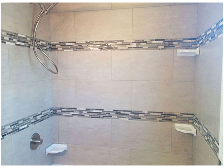 Tiled walls surround bathtub with mosaic tile accent borders