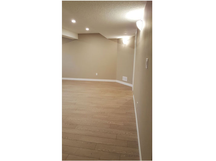 Basement living room space with oak laminate flooring