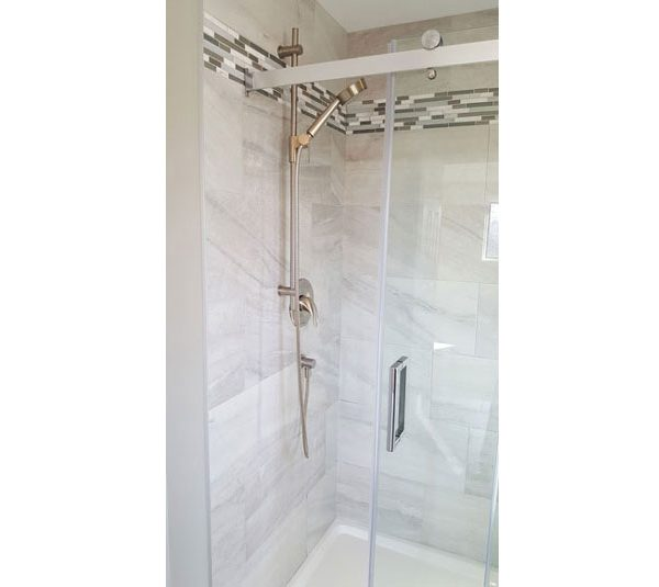 Walk-in shower with porcelain subway tiled walls and mosaic tile accent border