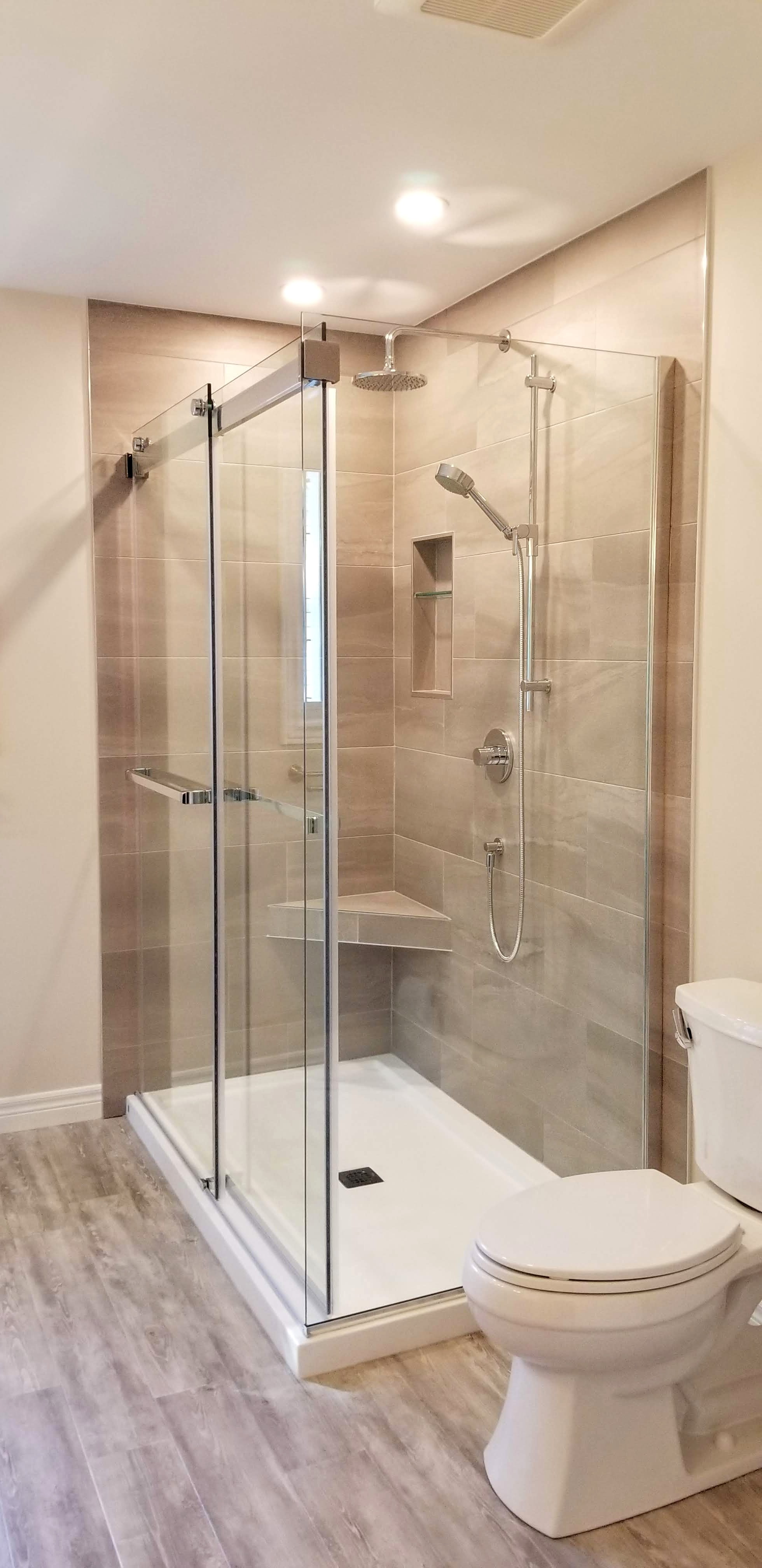 Tiled shower enclosed by glass door and panels by Germano Creative Interior Contracting Ltd.