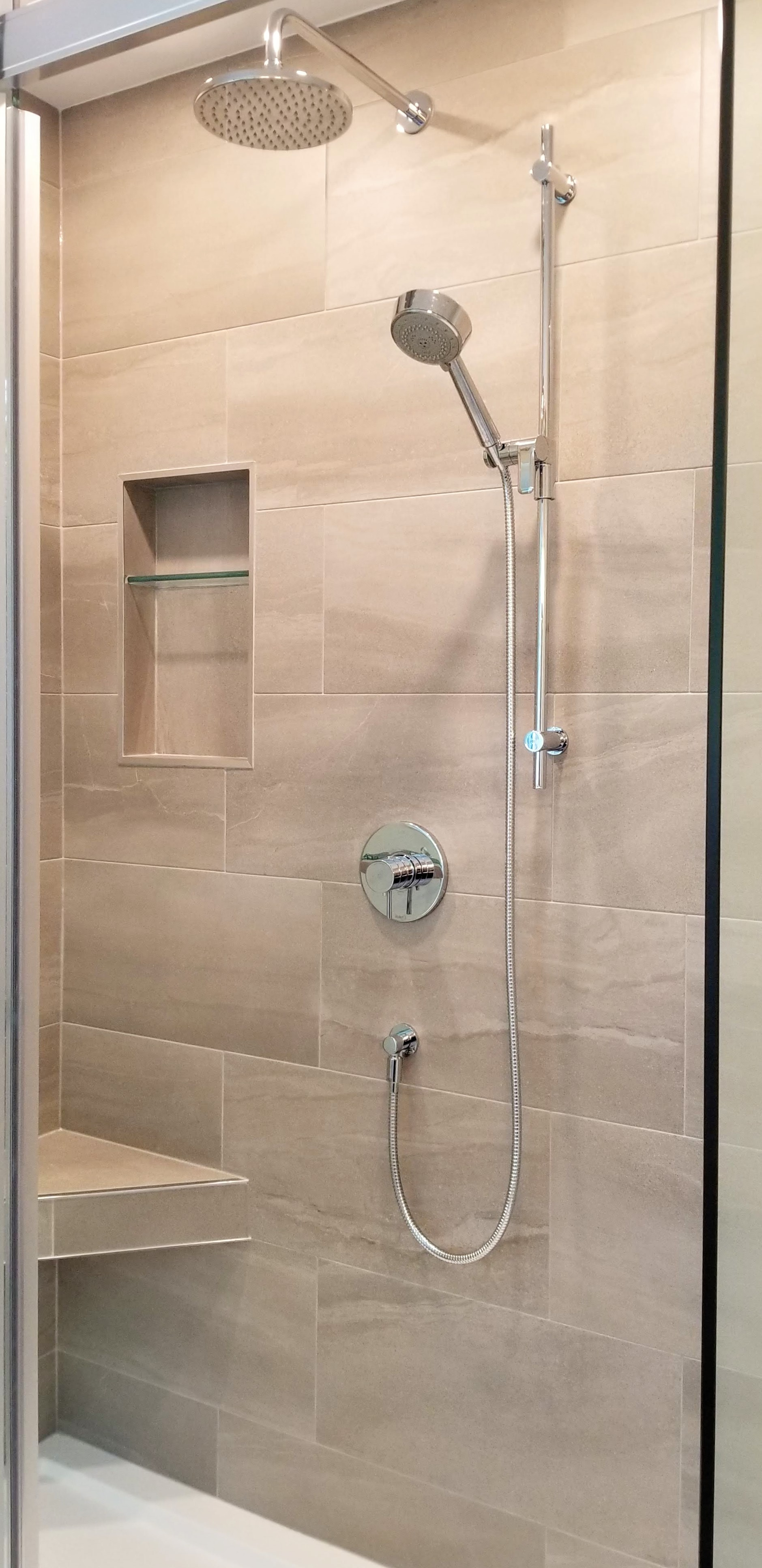 Tiled shower with niche installed in ensuite bathroom by Germano Creative Interior Contracting Ltd.