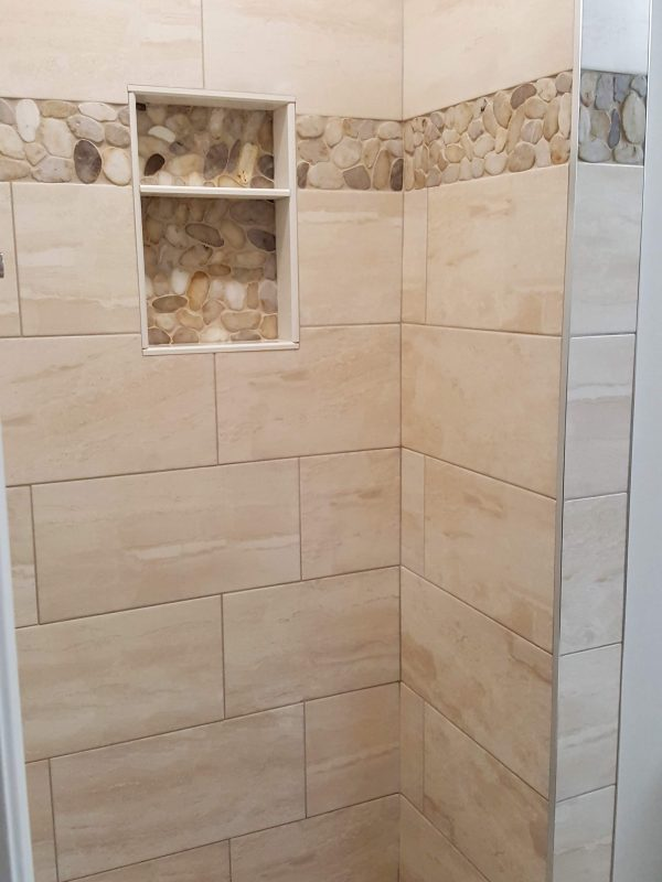 Shower niche with pebble stone accent border