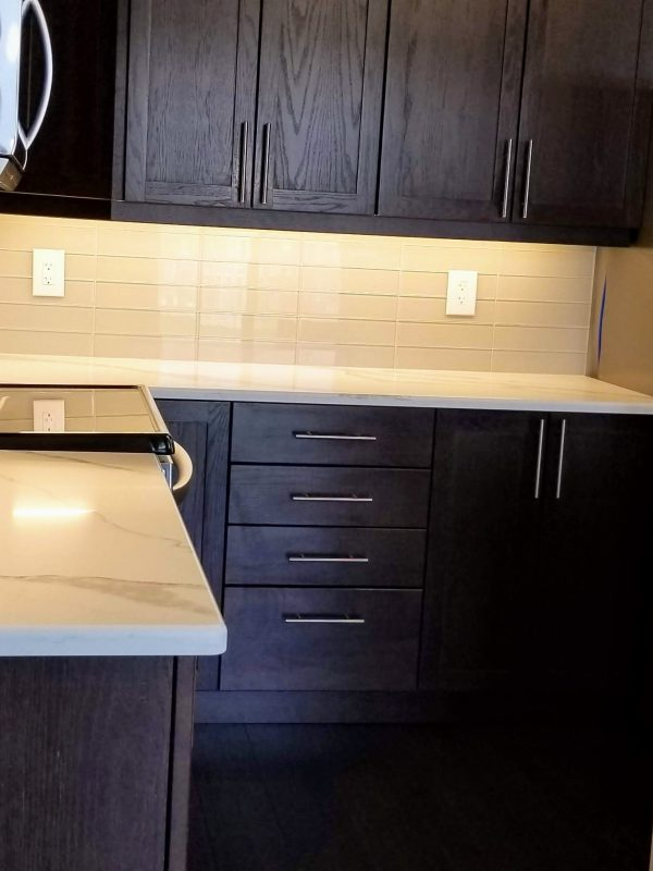 White quartz countertops with a glass tile backsplash