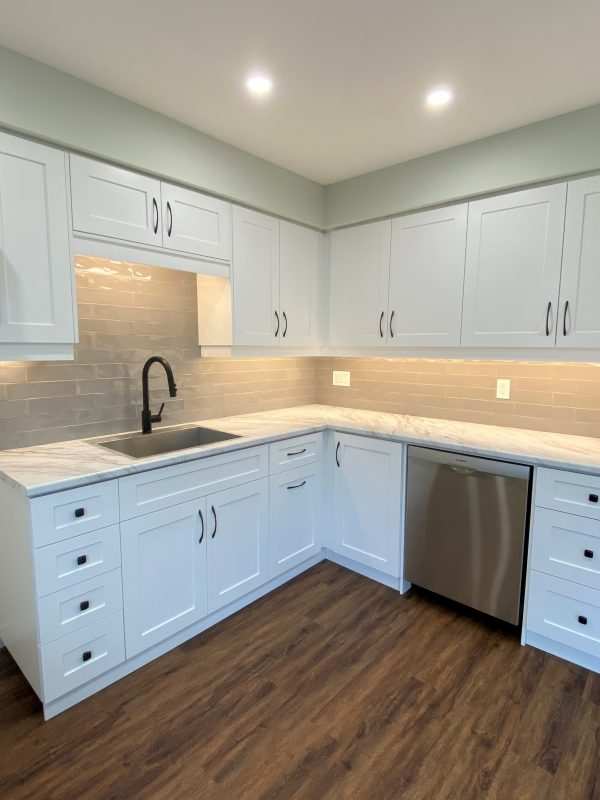 White shaker style kitchen cabinets featuring a laminate countertop