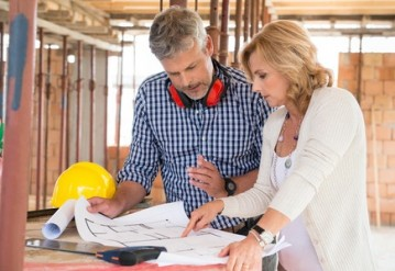 Male architect and woman discussing blueprint plan at construction site