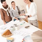 Female interior designer with two clients at office making selections