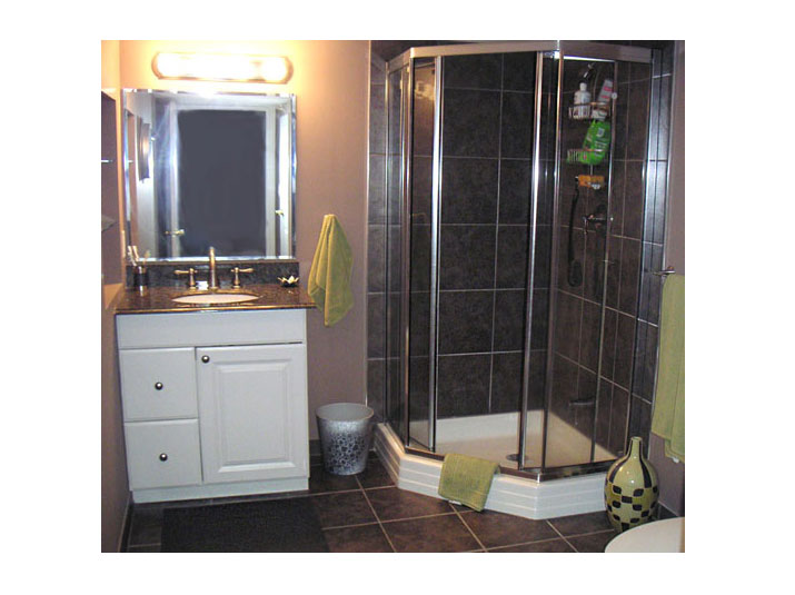 Corner shower with glass doors and tiled walls