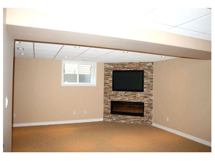 Fireplace with stone accent wall in basement family room
