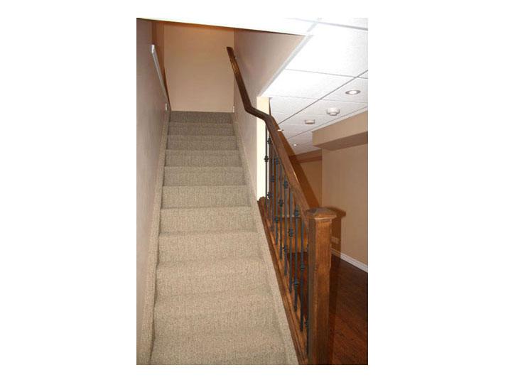 Oak railing and berber carpet for basement stairs