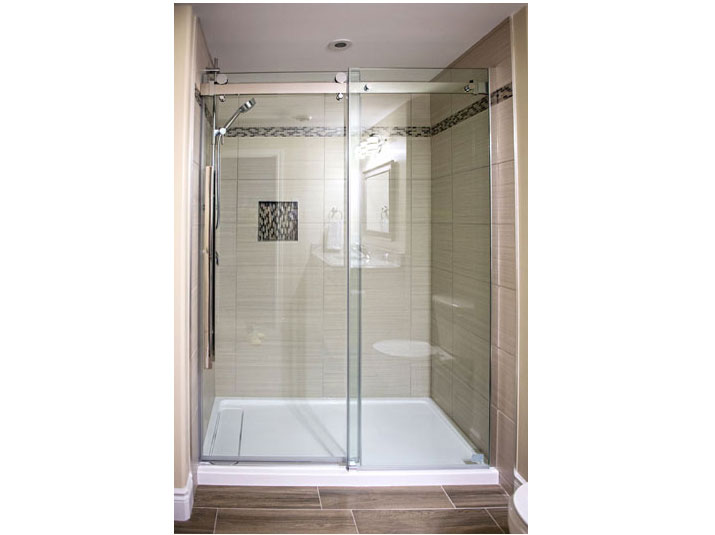 Tiled shower with frameless glass door and panel