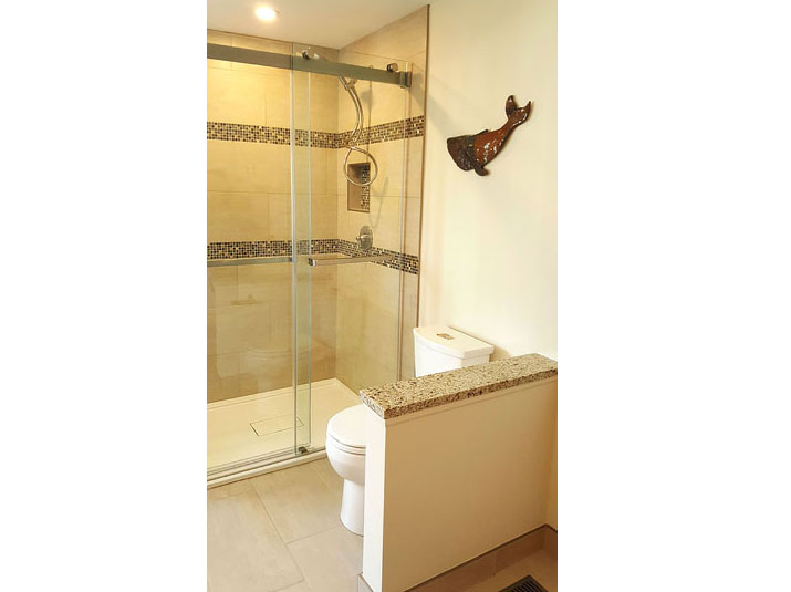 Glazed porcelain tiled shower surround with mosaic tile accent borders