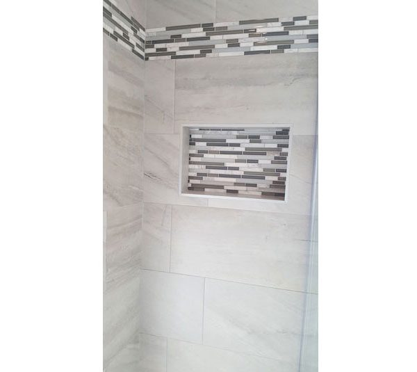 Shower niche with stone and glass mosaic tile