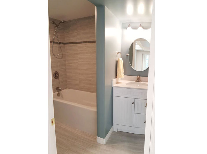 Three-piece bathroom with alcove shower with gray glazed porcelain subway tiles