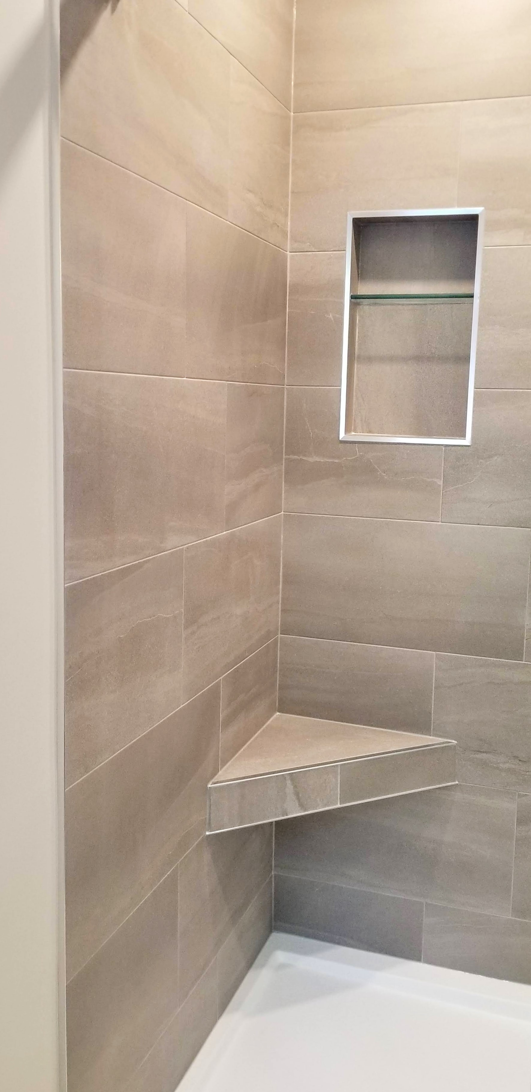 Tiled floating shower bench in tiled shower by Germano Creative Interior Contracting Ltd.