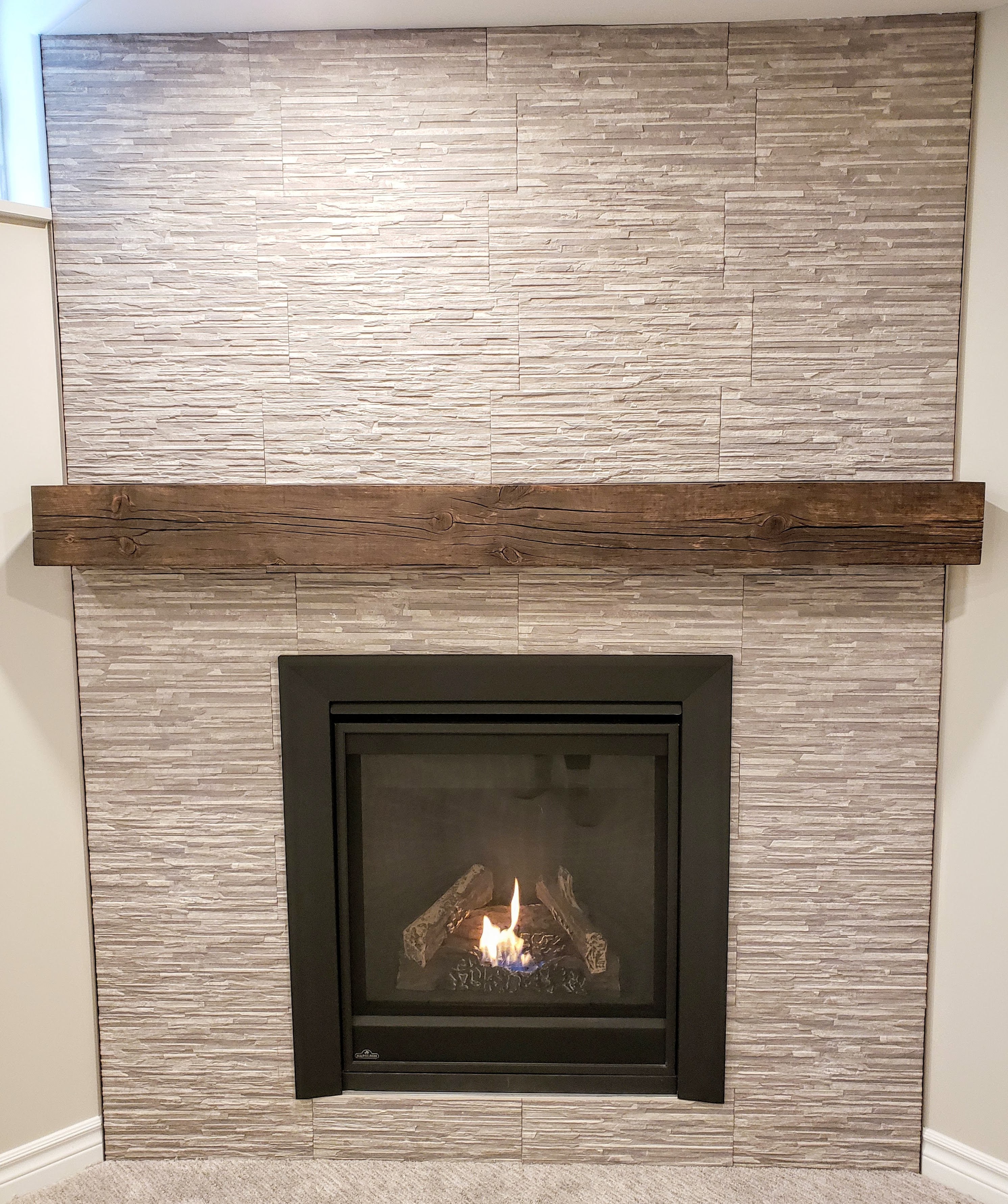 Fireplace tile surround and barn beam mantel by Germano Creative Interior Contracting Ltd.