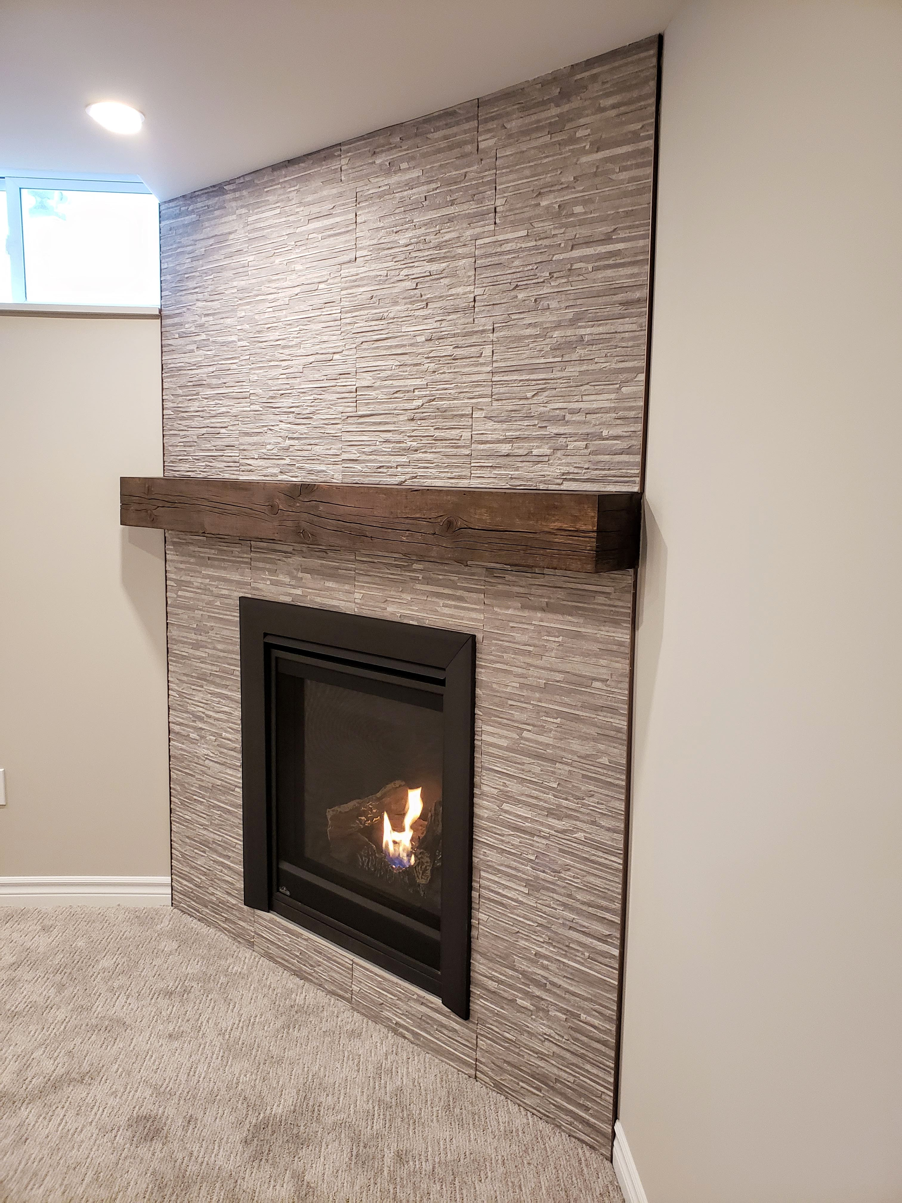 Basement fireplace with tile surround and rustic mantel by Germano Creative Interior Contracting Ltd.