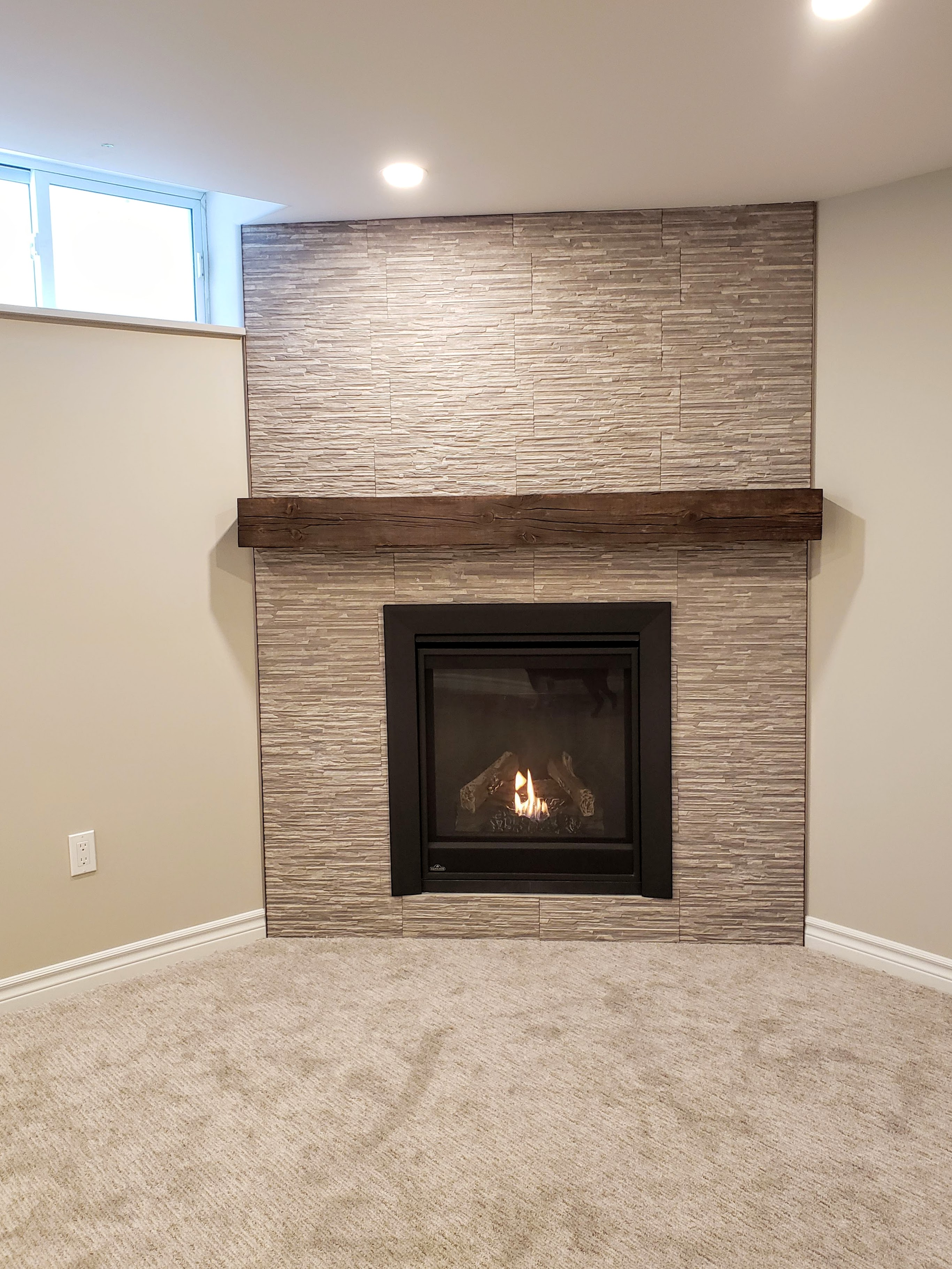 Gas fireplace with tile surround and rustic mantel by Germano Creative Interior Contracting Ltd.