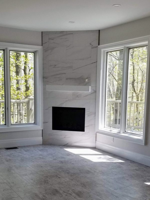 Fireplace featuring white marble tile surround and white mantel